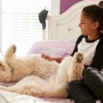 A young teen girl petting her dog on her bed